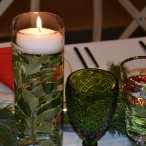 Glass votives were filled with holly leaves or cranberries, topped with a candle and placed along the center of the dining table.