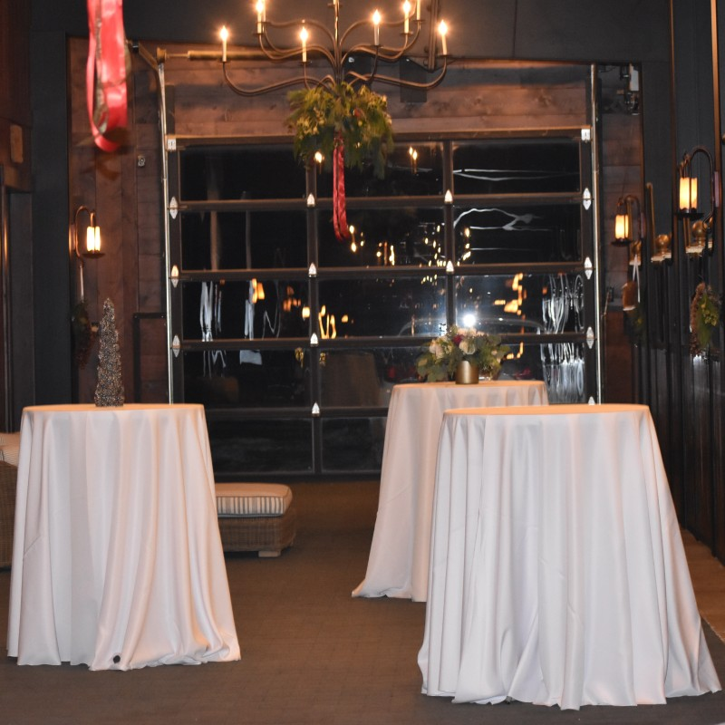 Hightop tables were placed in front of the horse stalls for cocktail hour socializing.
