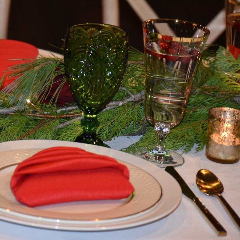 Festive red napkins were shaped into Christmas trees for a whimsical pop of color atop plain white plates.