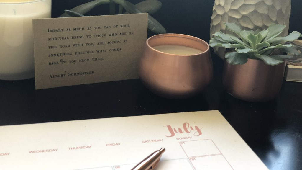 Quotes, planner and plant pots on desk